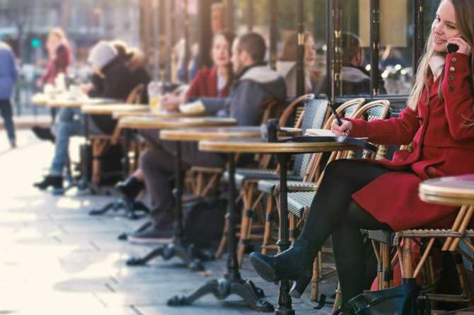 Woman talks on the phone at a Paris cafe 1655x745