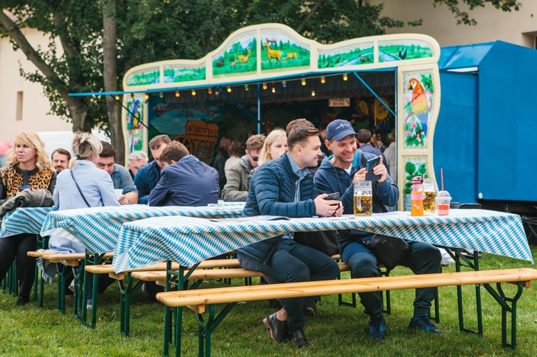 Two men look at their phones at a beer fest in Germany